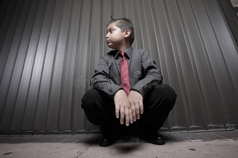 男孩生意人蹲年轻人 免版税库存图片
