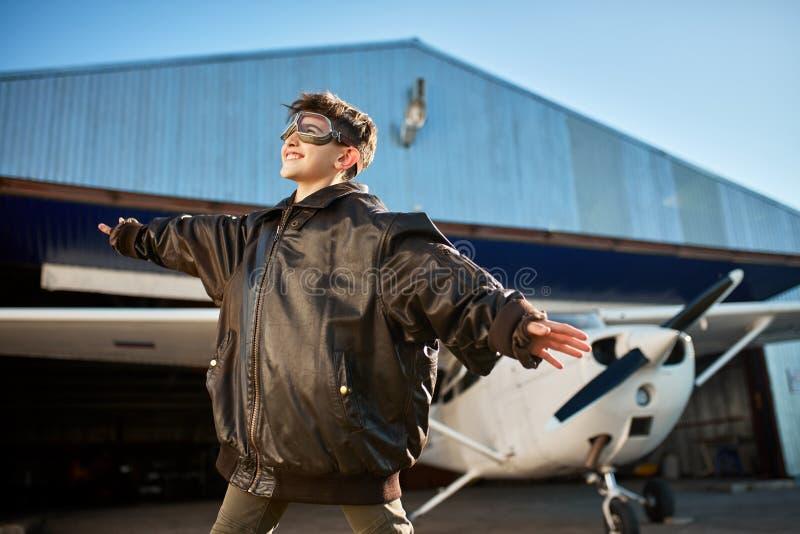 男孩用分开手象翼,站立飞机棚外,大试验夹克的 库存图片