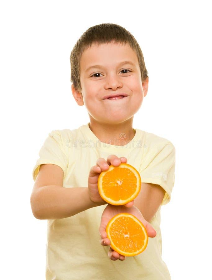 男孩用切的桔子 免版税库存照片