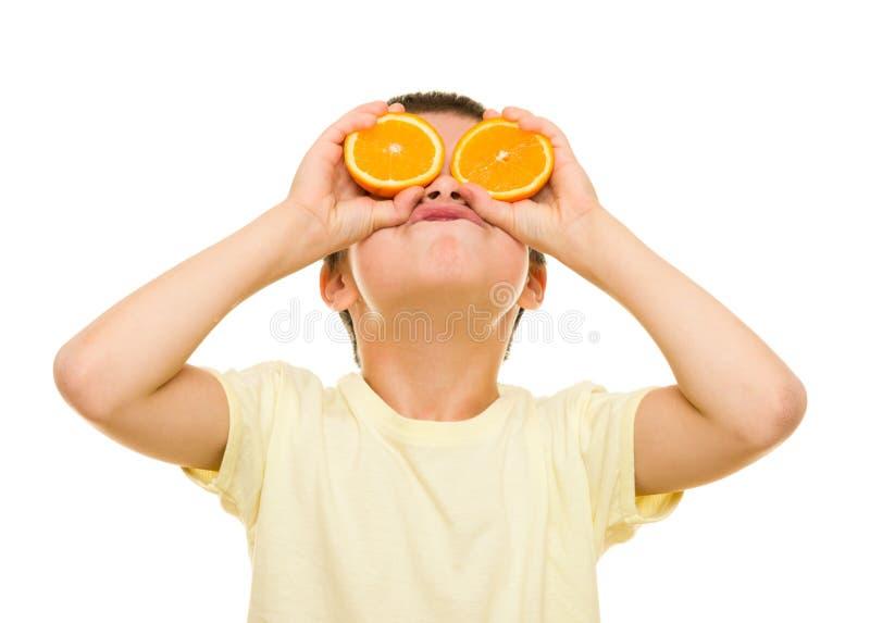 男孩用切的桔子 免版税库存图片