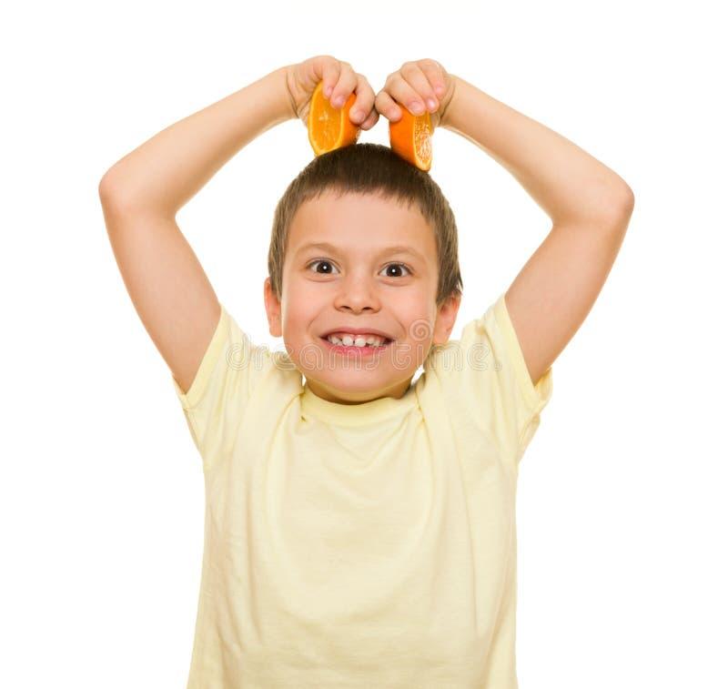 男孩用切的桔子 库存图片