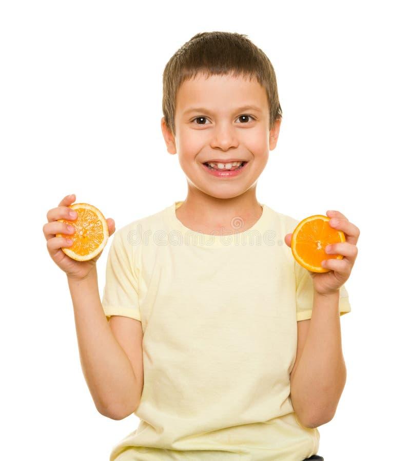 男孩用切的桔子 免版税图库摄影