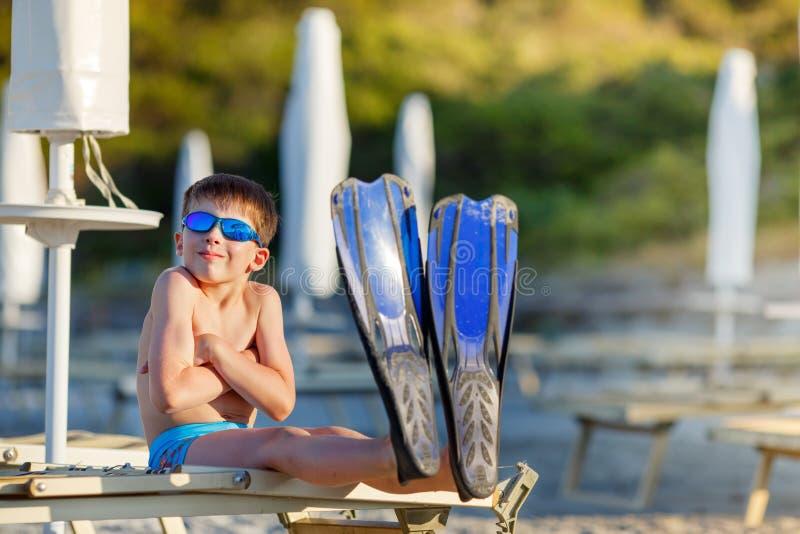 男孩用在热带海滩的潜航的设备 免版税库存图片