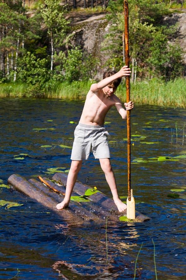 男孩用筏子运送 库存图片