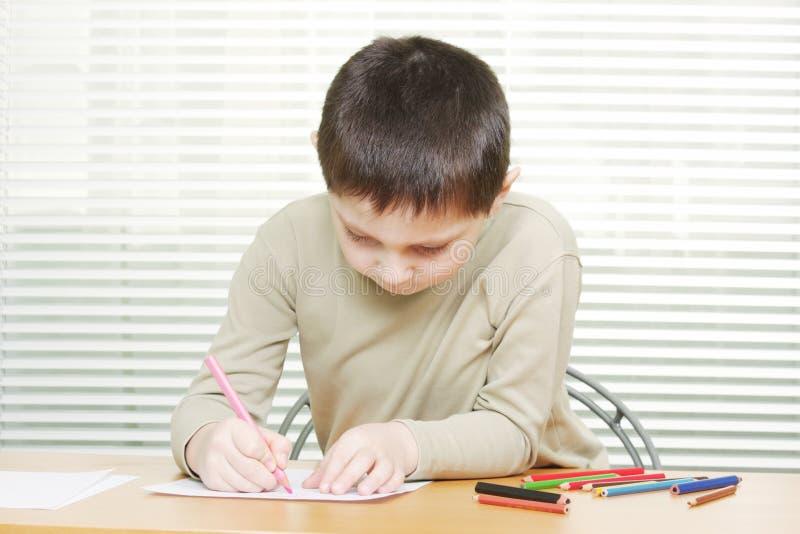 男孩用蜡笔画逗人喜爱的服务台图画 库存照片