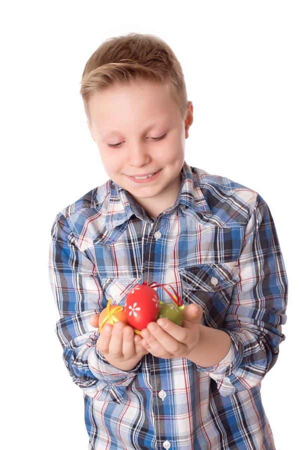 年轻男孩用他的在白色的复活节彩蛋 库存照片