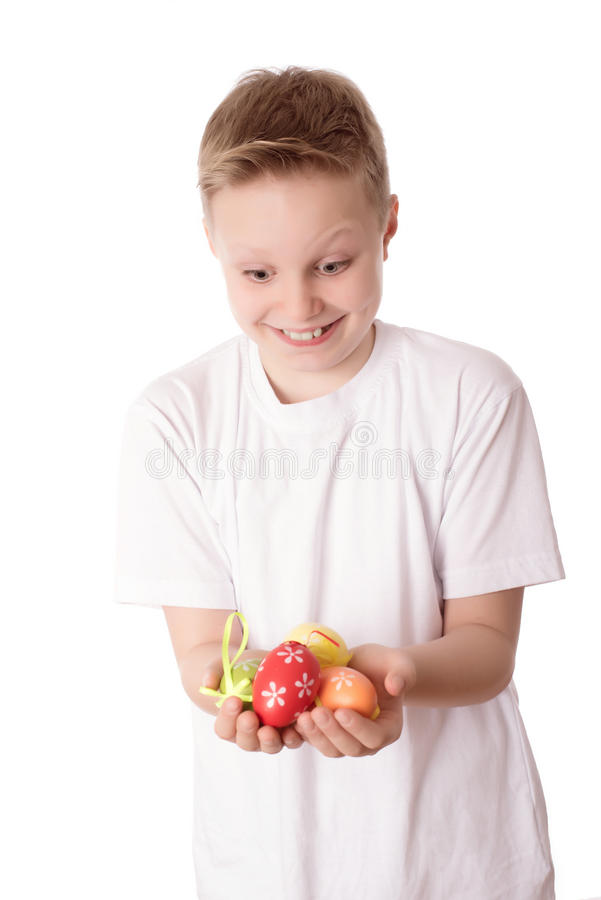 年轻男孩用他的在白色的复活节彩蛋 免版税图库摄影