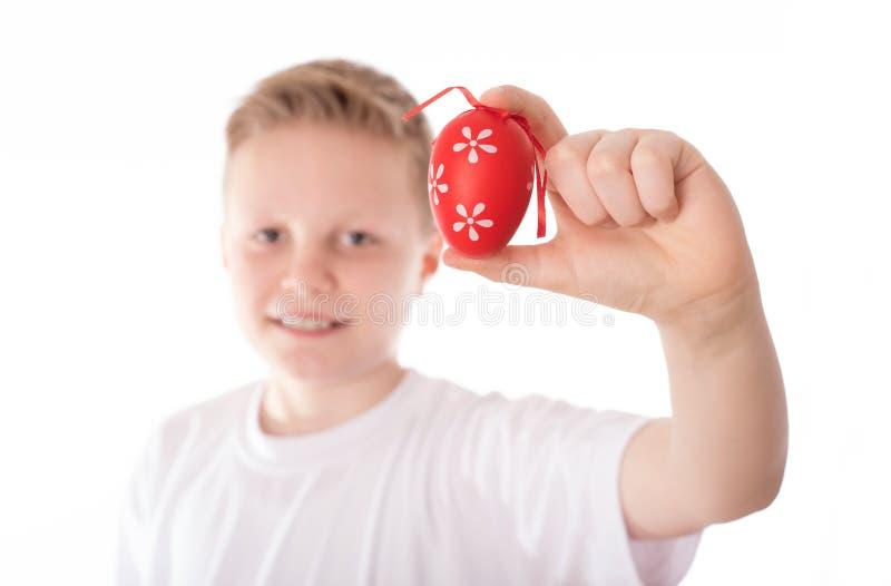 年轻男孩用他的在白色的复活节彩蛋 免版税库存图片