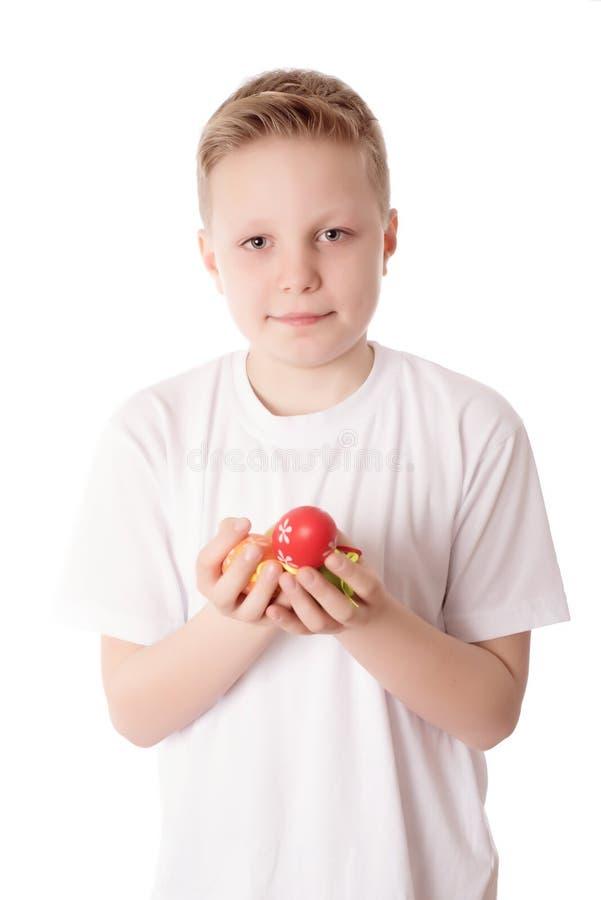 年轻男孩用他的在白色的复活节彩蛋 免版税库存照片