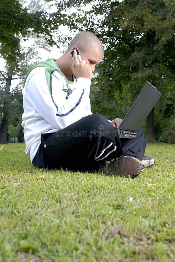 男孩电池笔记本公园电话 免版税图库摄影
