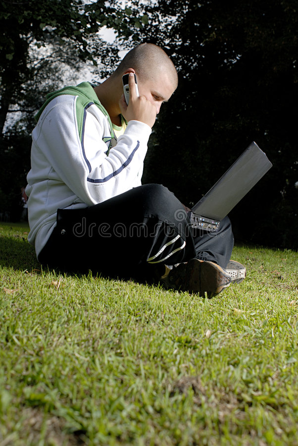 男孩电池笔记本公园电话 图库摄影