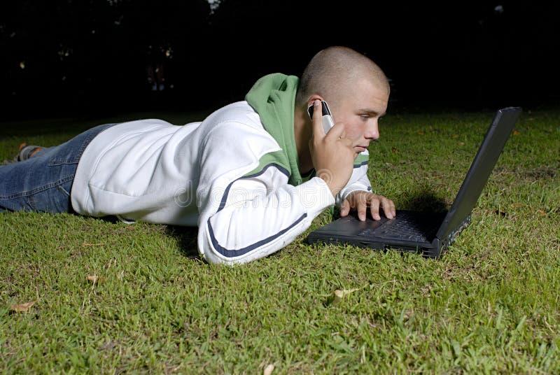 男孩电池笔记本公园电话 免版税库存图片