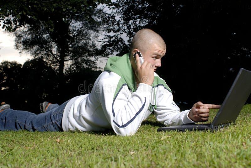 男孩电池笔记本公园电话 库存图片