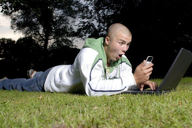 男孩电池笔记本公园电话 免版税库存照片