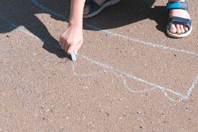 男孩画与在沥青的蓝色白垩 特写镜头手 库存图片