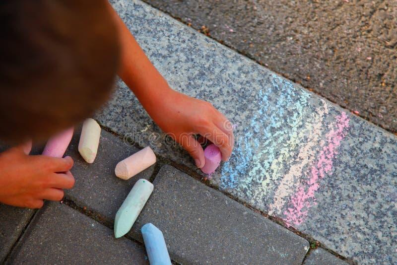 男孩画在路面的彩虹色的白垩 免版税图库摄影