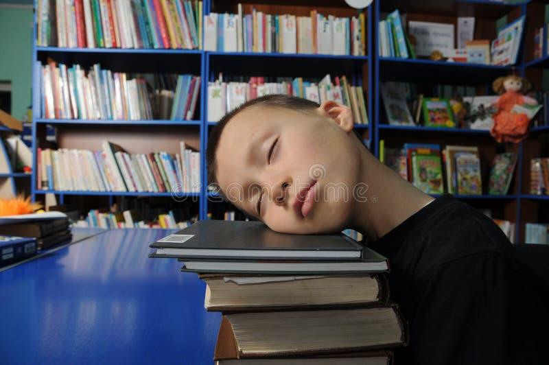 男孩疲乏睡觉在堆书在图书馆里exausted教育 免版税图库摄影