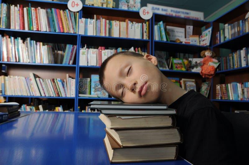 男孩疲乏睡觉在堆书在教育exausted的图书馆里 免版税图库摄影