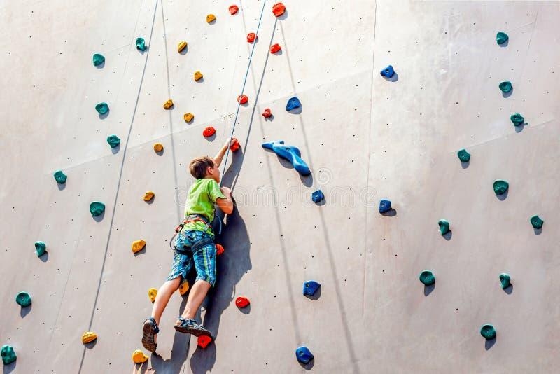 男孩登山人在一个人为塔上升,克服在他的途中的障碍  免版税库存图片