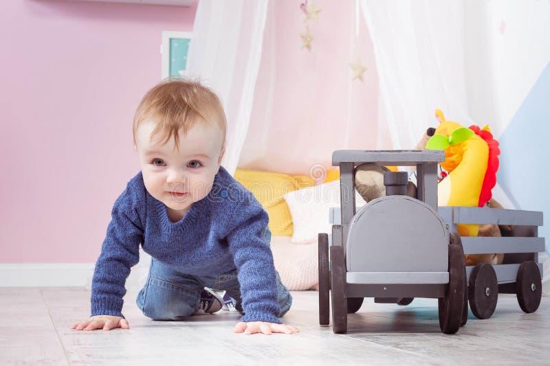 男孩白肤金发在一件蓝色毛线衣在一个木地板上爬行 使用与木玩具的一岁的婴孩 库存照片