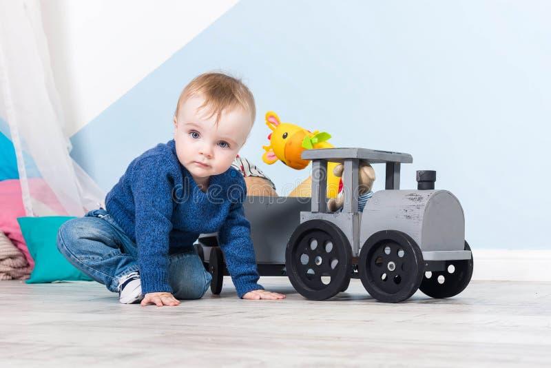 男孩白肤金发在一件蓝色毛线衣坐一个木地板 使用与木玩具的一岁的婴孩 火车由木头制成,与girafe 库存图片