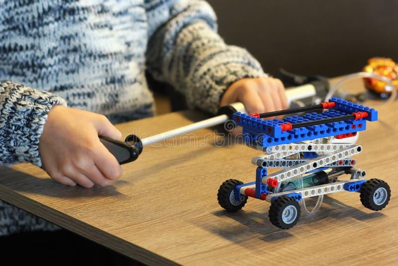 男孩的手特写镜头加大建设者和学会灵魂的基本在学校 机器人学 免版税库存照片