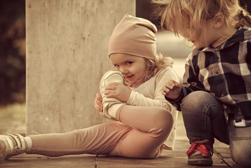男孩看看女孩与体育鞋子的接触鼻子 库存图片