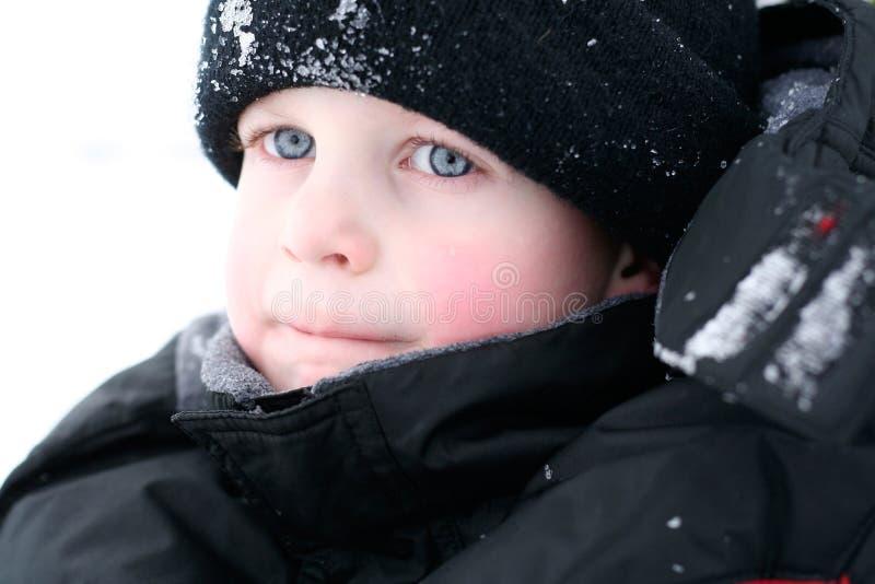 男孩看起来贯穿的雪 免版税库存照片