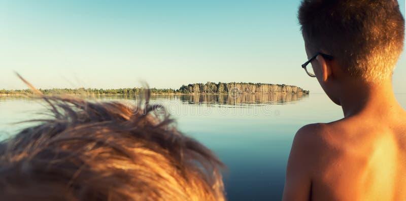 男孩看风平浪静和海岛 免版税库存图片