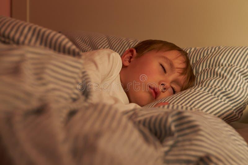 年轻男孩睡着在床上在晚上 库存图片