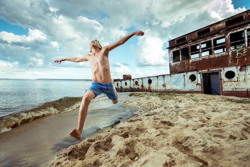 男孩短裤是愉快的跃迁并且翻转在海滩 免版税库存图片