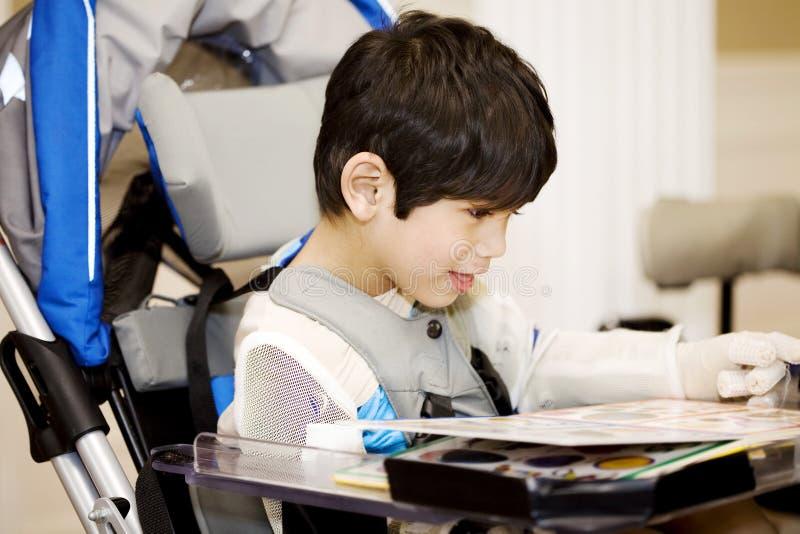 男孩禁用了四老学习的轮椅年 免版税库存图片