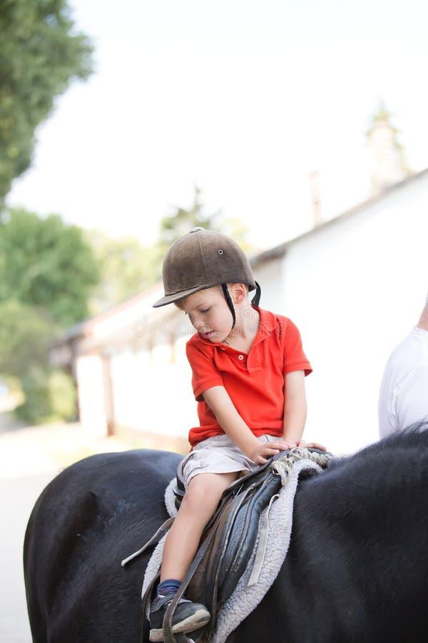 男孩穿橙色衬衣的和坐在马顶部的盔甲 免版税库存图片