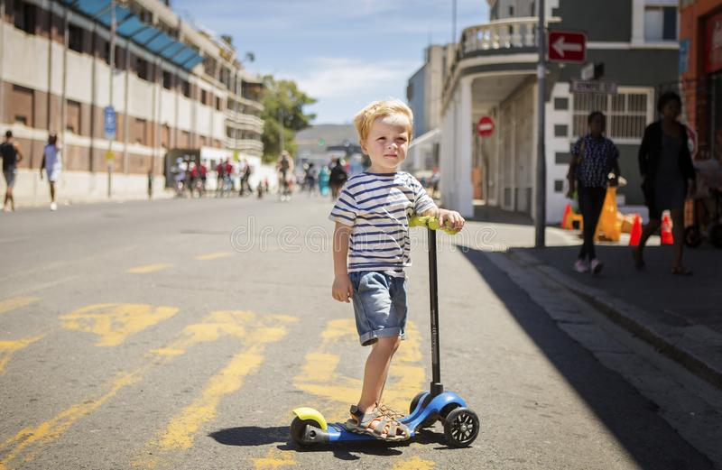 男孩站立与在都市街道的推挤自行车 免版税图库摄影