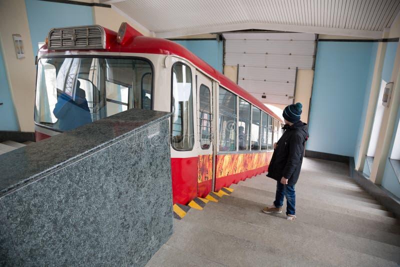 男孩站立在入口到缆索铁路的汽车 免版税图库摄影