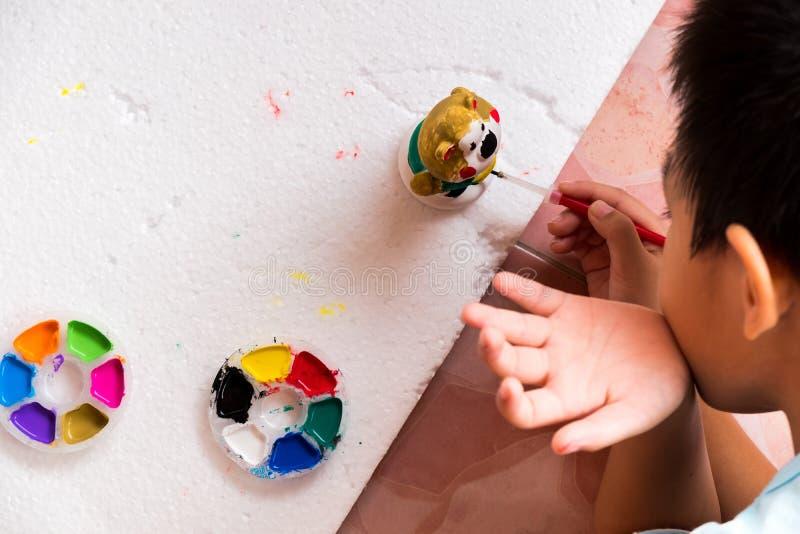 男孩绘他的与五颜六色的颜色的雕塑被te跟随 免版税库存照片