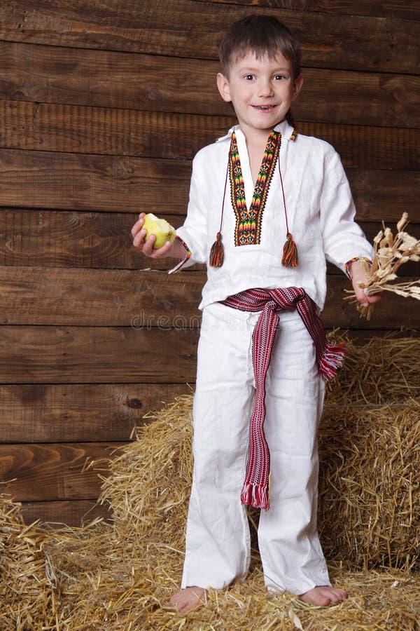 男孩给东欧传统穿衣 免版税图库摄影