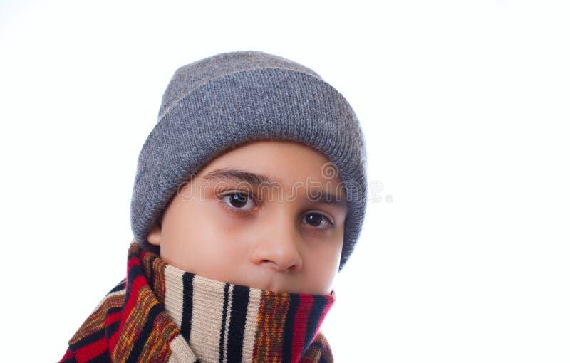 男孩给冬天穿衣 库存图片