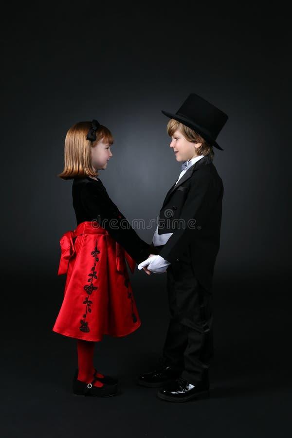 男孩给正式女孩年轻人穿衣 免版税图库摄影