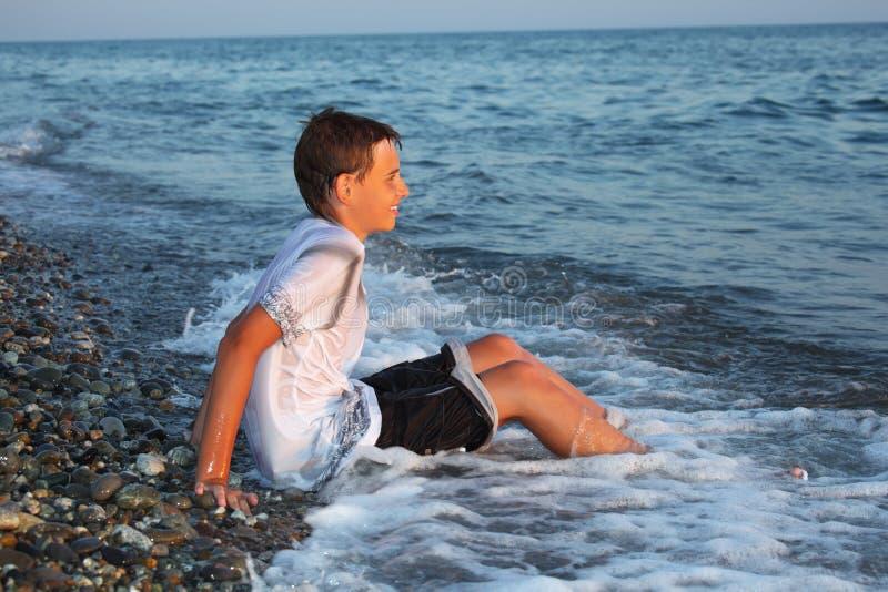 男孩给湿海岸坐的少年穿衣 库存图片
