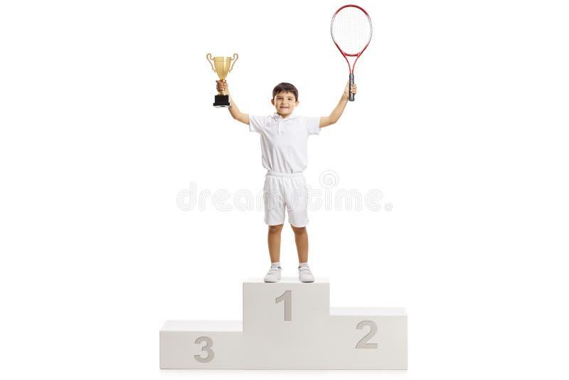 男孩网球在垫座的优胜者身分 免版税库存照片