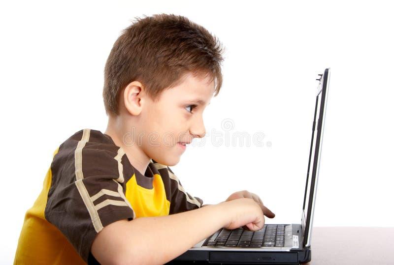 男孩膝上型计算机工作 库存图片