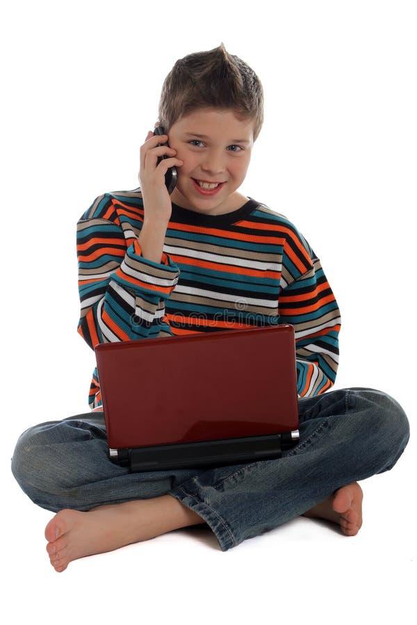男孩膝上型计算机电话使用 免版税库存照片