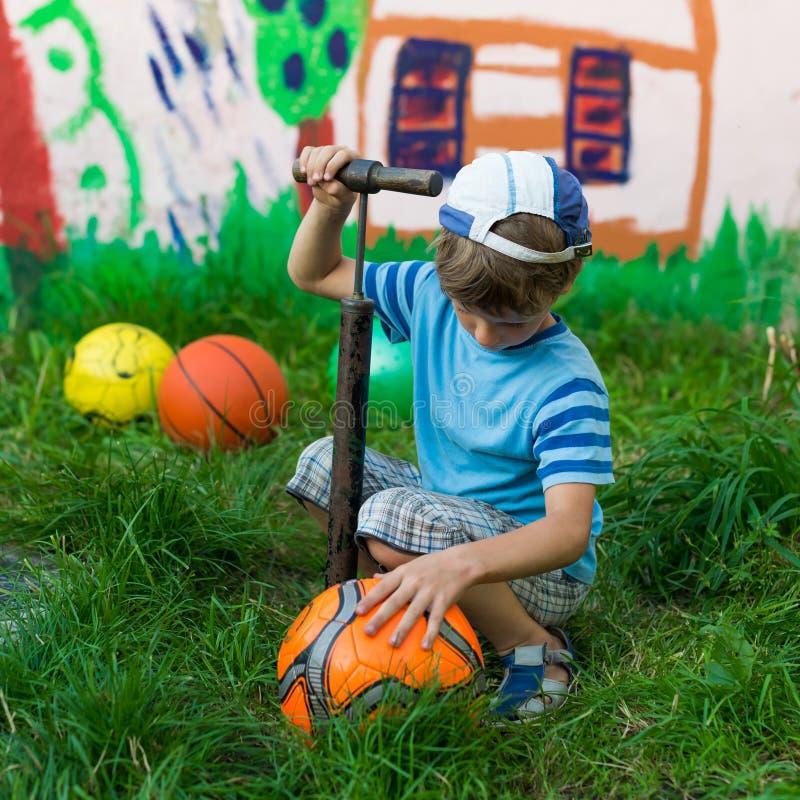 男孩膨胀足球泵浦 免版税库存图片