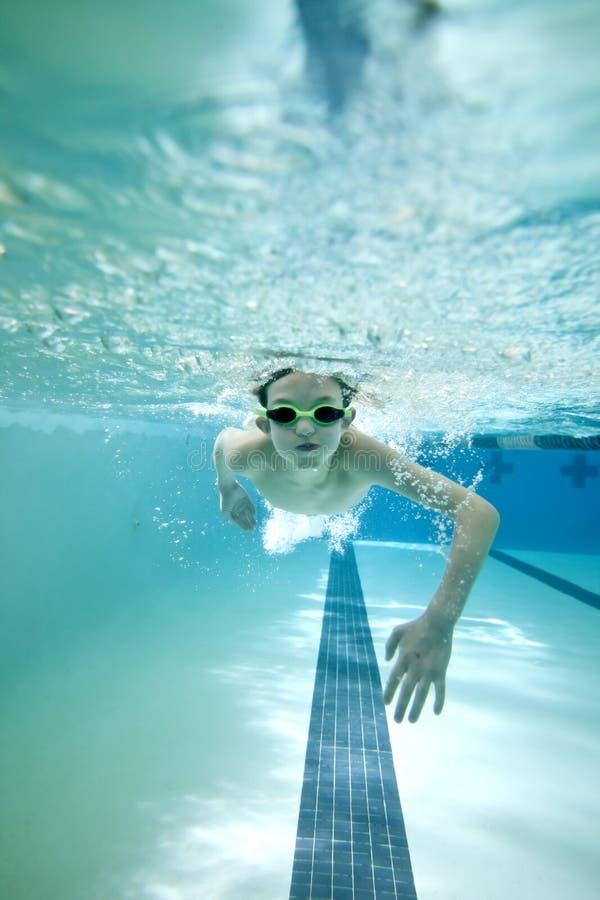 男孩舔游泳 免版税库存图片
