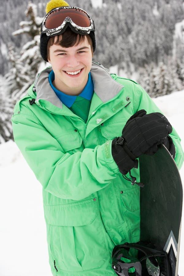 男孩节假日少年滑雪的雪板 图库摄影