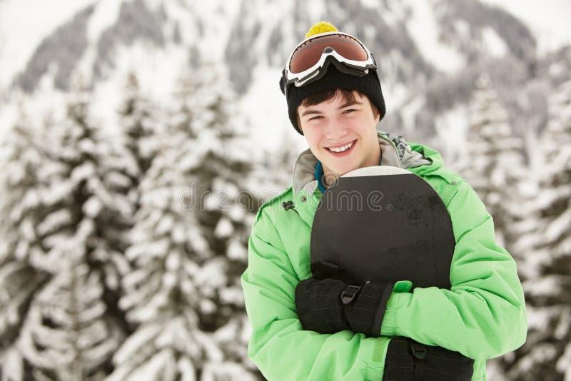 男孩节假日少年滑雪的雪板 库存照片