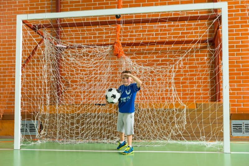 年轻男孩获得乐趣作为足球守门员 免版税库存图片