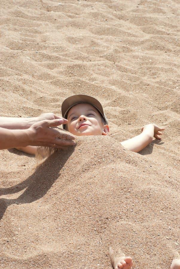 男孩被埋没的沙子 免版税图库摄影