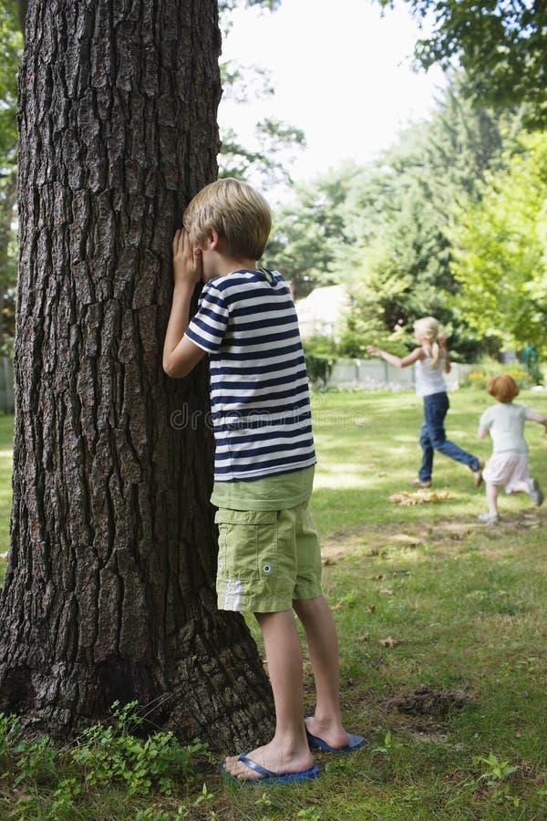男孩覆盖物眼睛在庭院里 免版税库存照片
